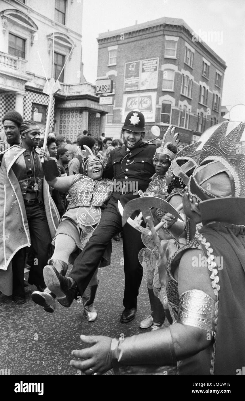 A policeman dances with a woman in costume at Notting Hill carnival. 28th August 1978. - Stock Image