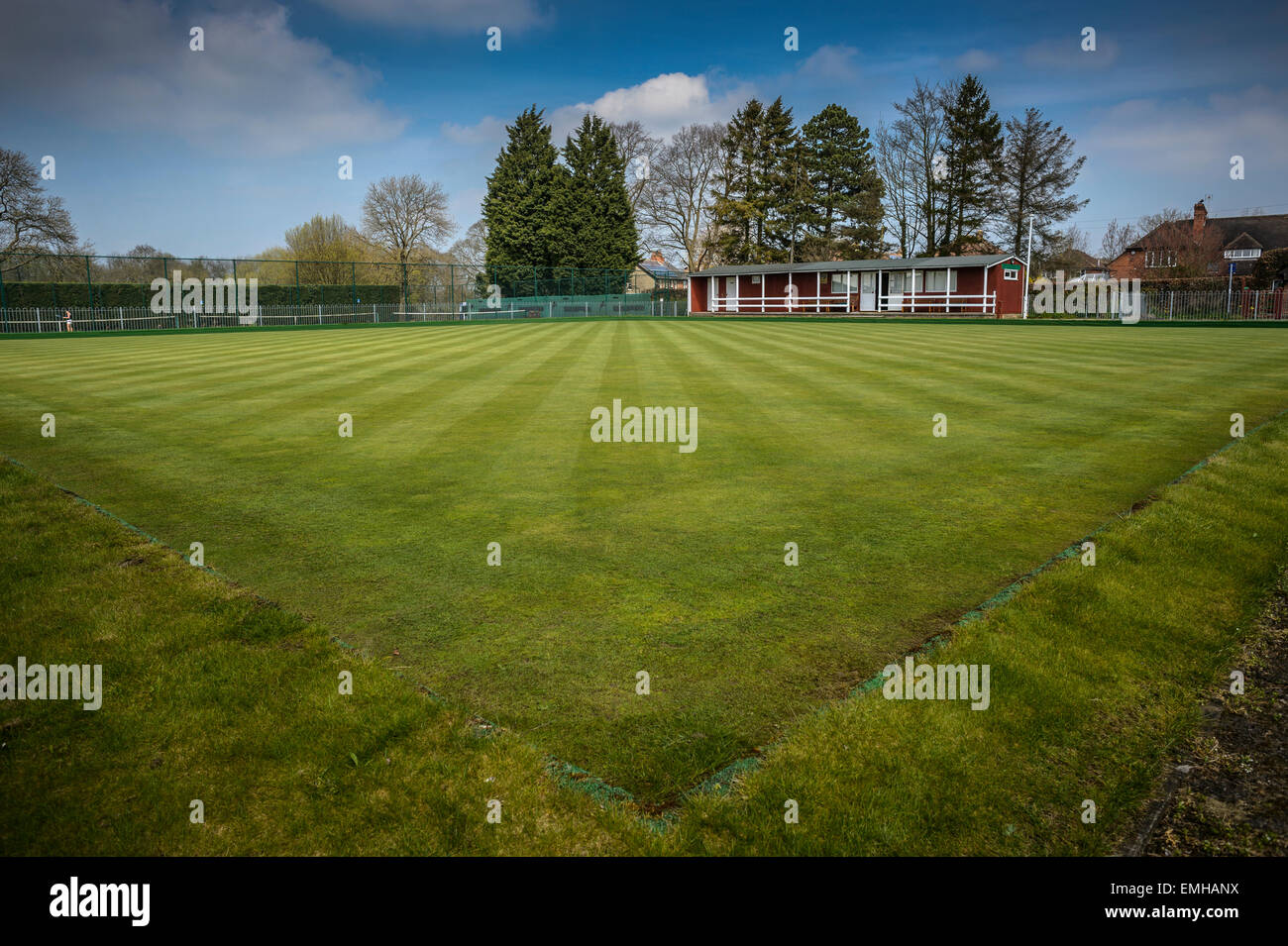 Freshly mowed lawn on a bowling green with clubhouse in background in a rural Yorkshire village. - Stock Image