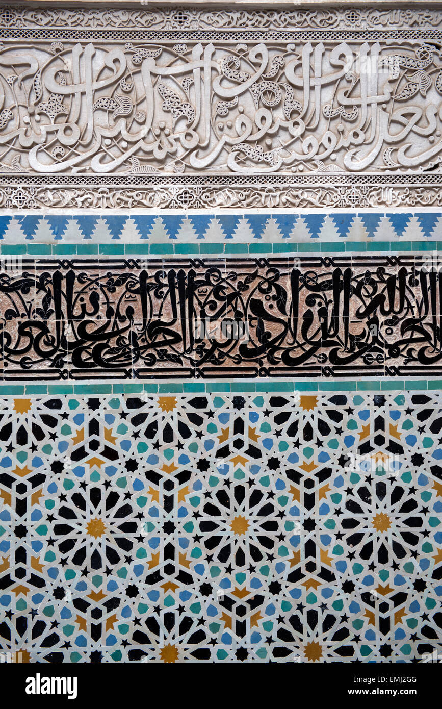 Al Attarine Madrasa, Koranic school, in Fes, Morocco.  Detail of Arabic script carved into tile, highest form of - Stock Image