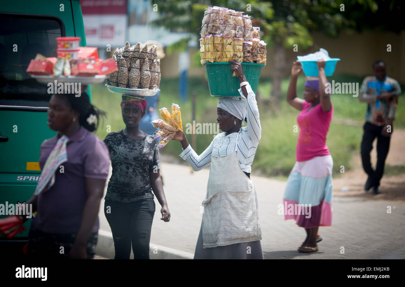 Salesladies balance their goods for sale on their heads as they walk across a main road in Accra, Ghana, 8 April - Stock Image