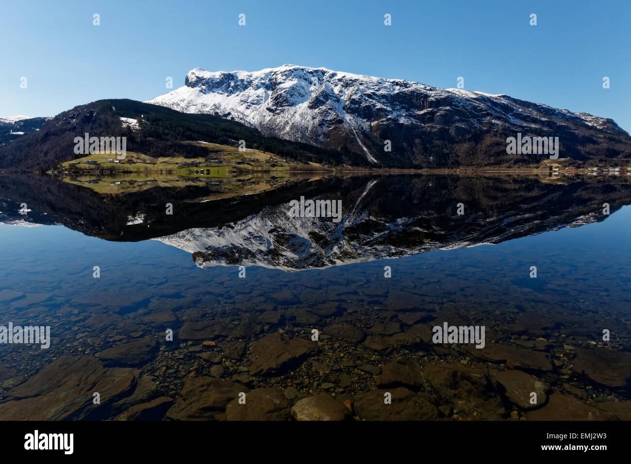 Reflection of the mountains meeting the sea at Granvinsvatnet, in Hardanger, Norway. Stock Photo