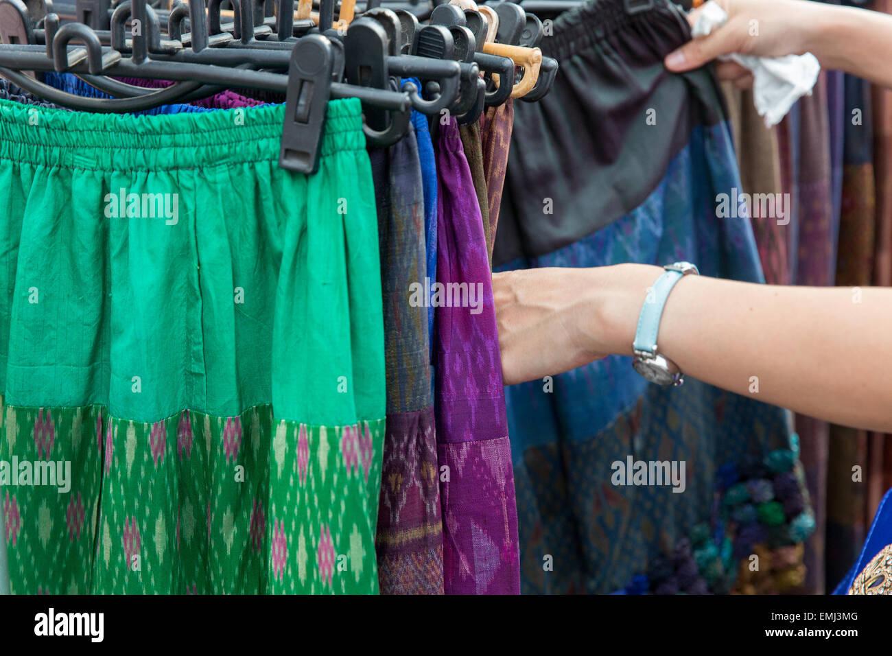 close up of hands choosing skirts at street market - Stock Image