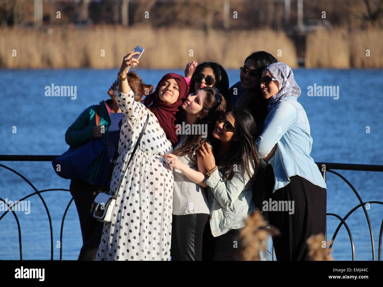 A group of female friends taking a selfie near a pond. - Stock Image
