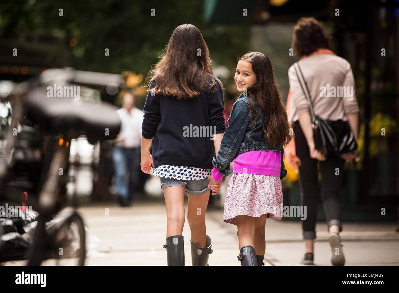 Two Young Girls Holding Hands While Walking Down Sidewalk ...