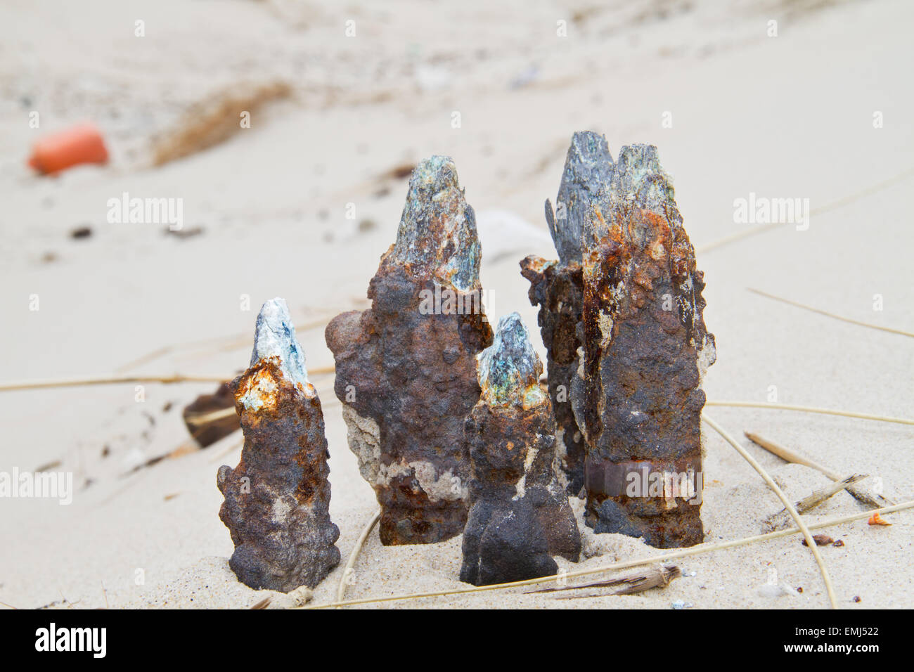 Rusty, oxidized ammunition, remainders of a war, found an a beach. - Stock Image