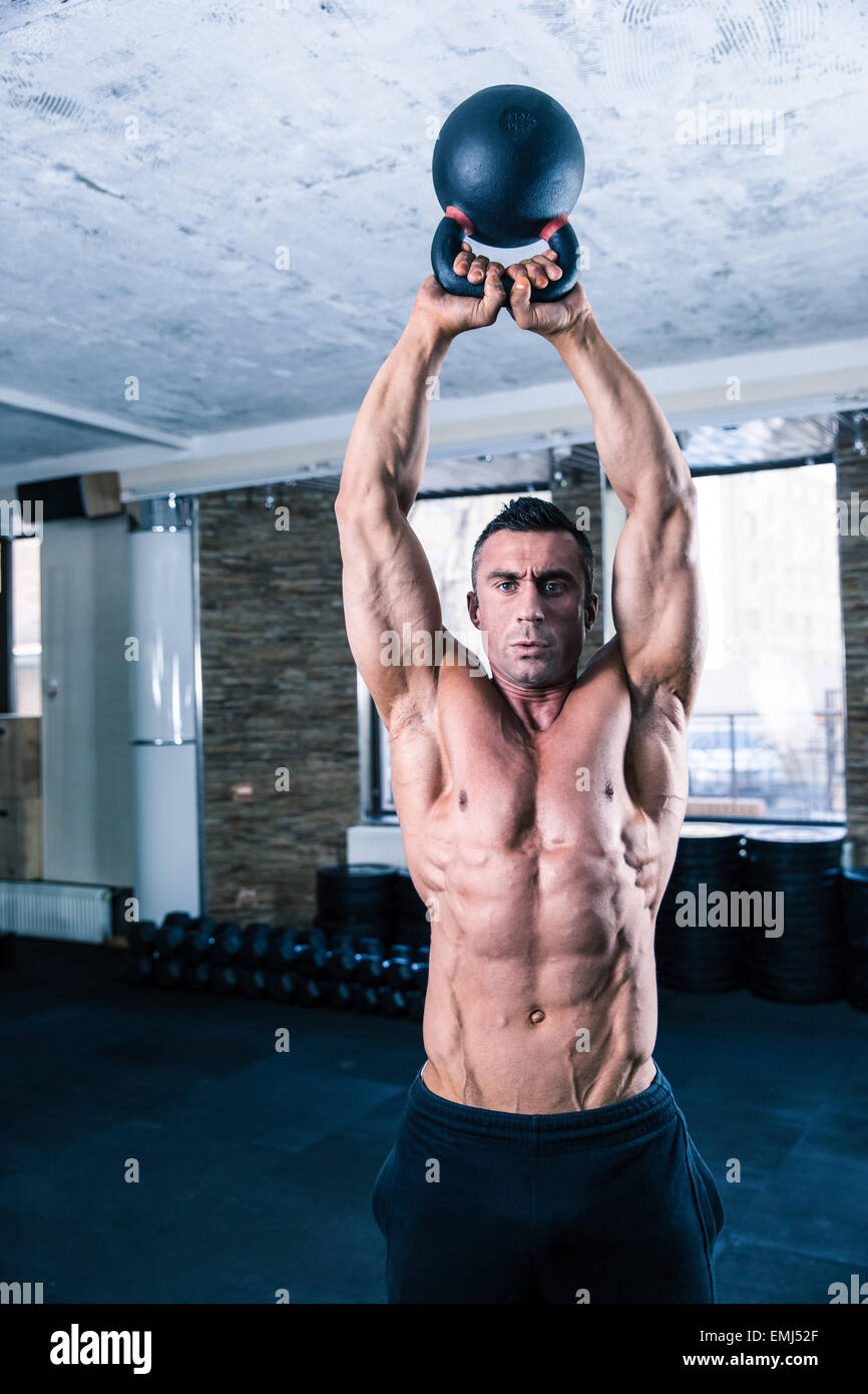 Handsome bodybuilder man workout with kettle ball in crossfit gym - Stock Image