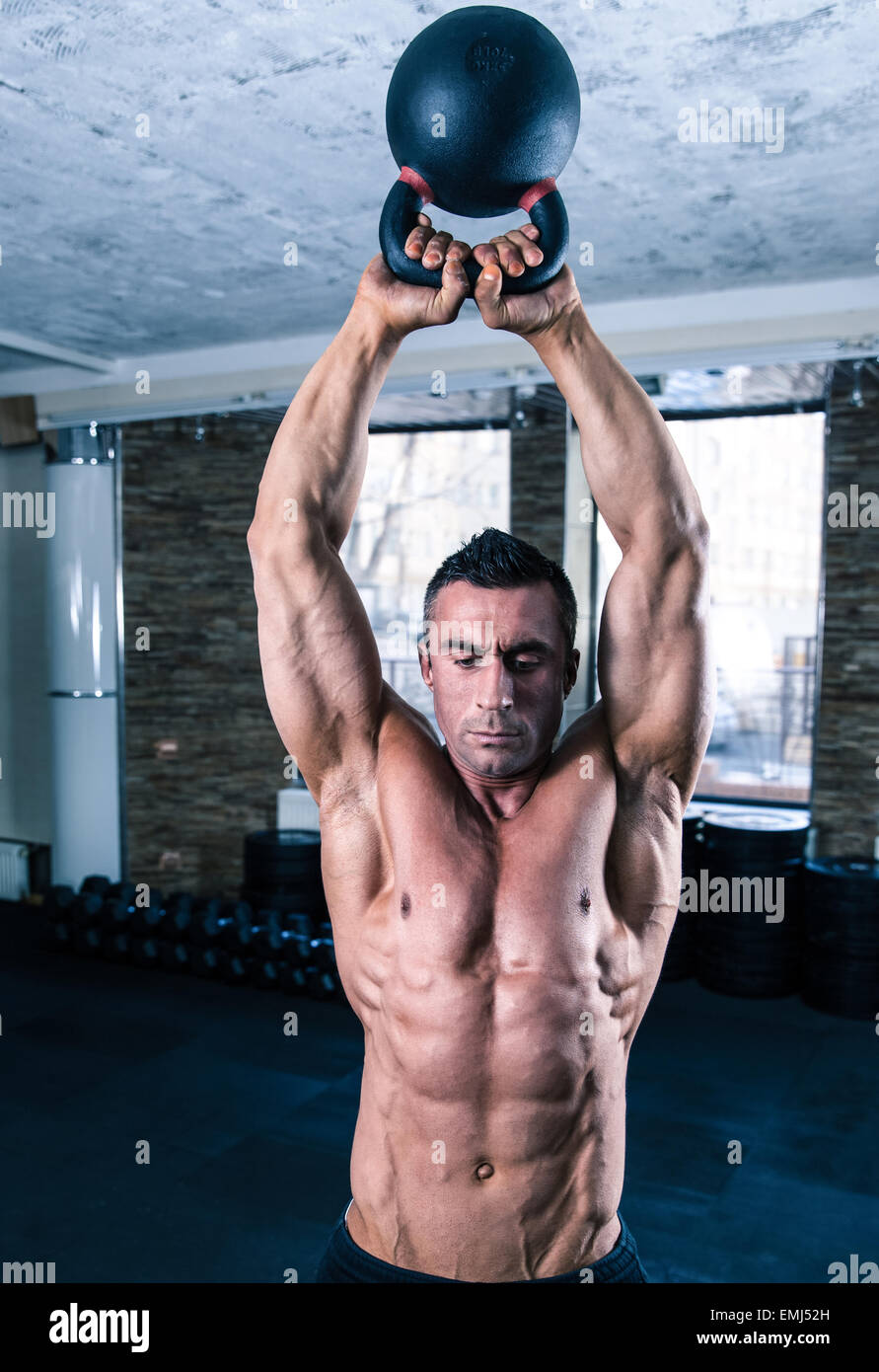 Bodybuilder man workout with kettle ball in crossfit gym - Stock Image