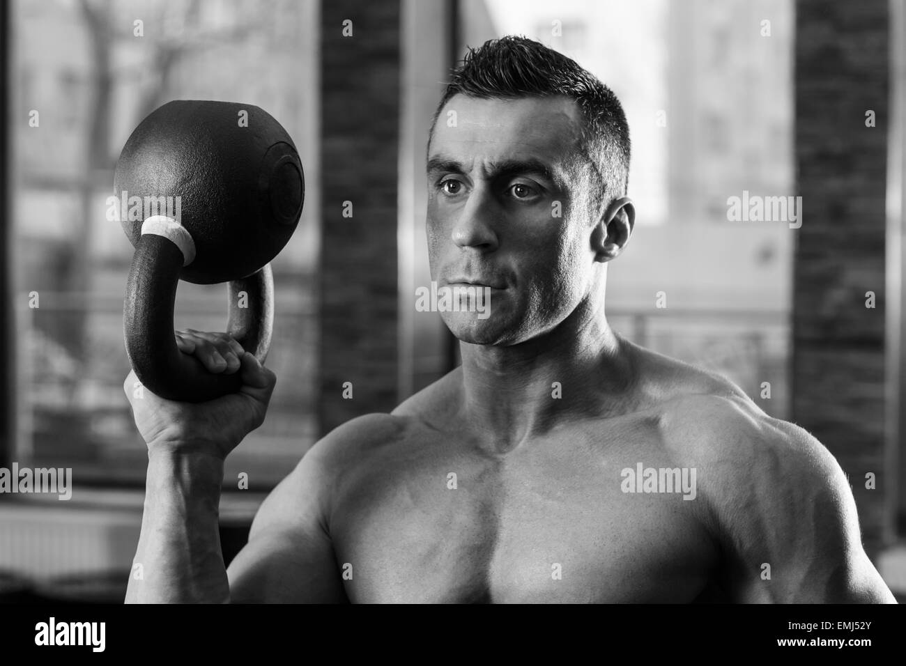 Black and white portrait of a bodybuilder holding kettle ball in gym - Stock Image
