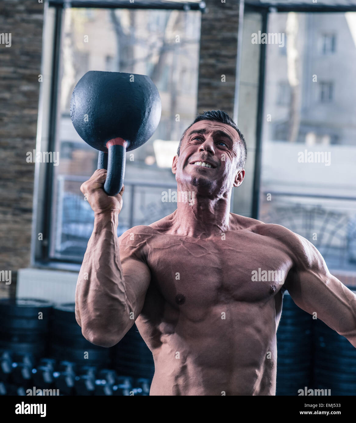 Bodybuilder man workout with kettle ball at gym - Stock Image