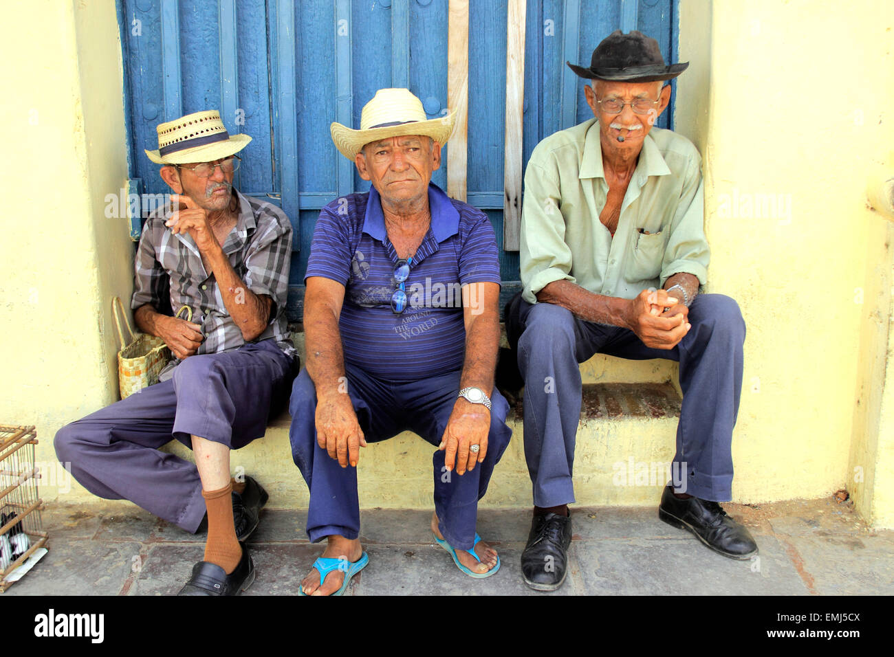 Three elderly gentlemen on a colorful street in Trinidad Cuba - Stock Image