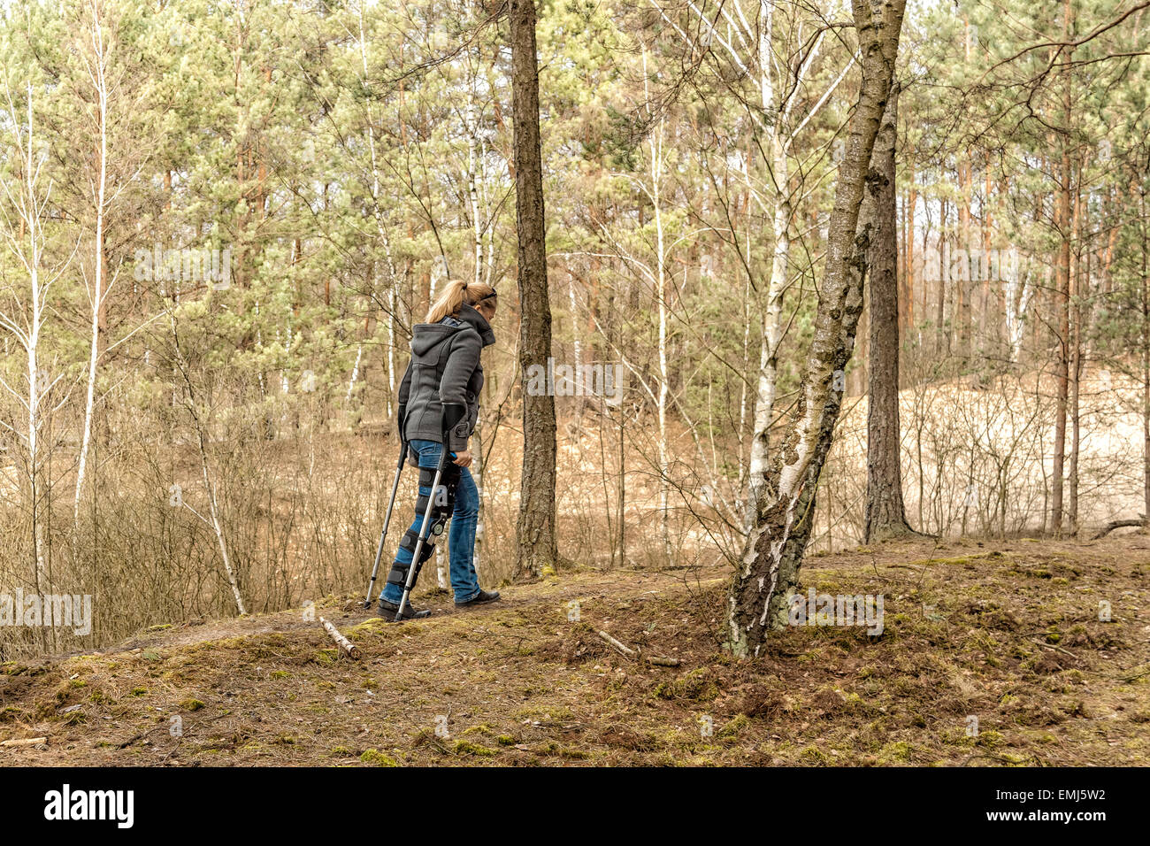 Adult woman in orthosis having a walk in Kampinos National Park, Poland - Stock Image