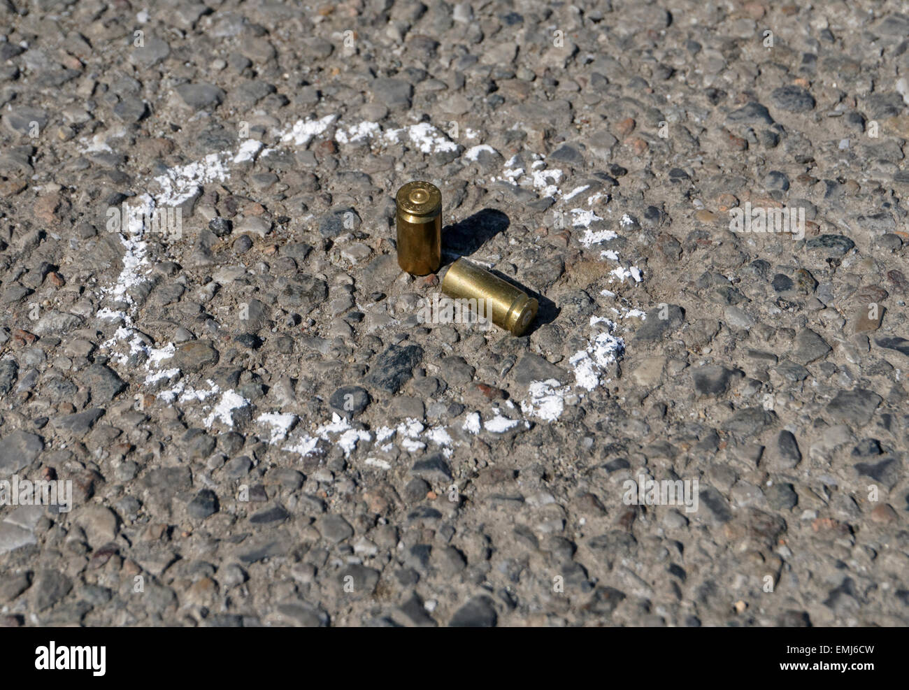 Bullets on ground with chalk drawn around - Stock Image