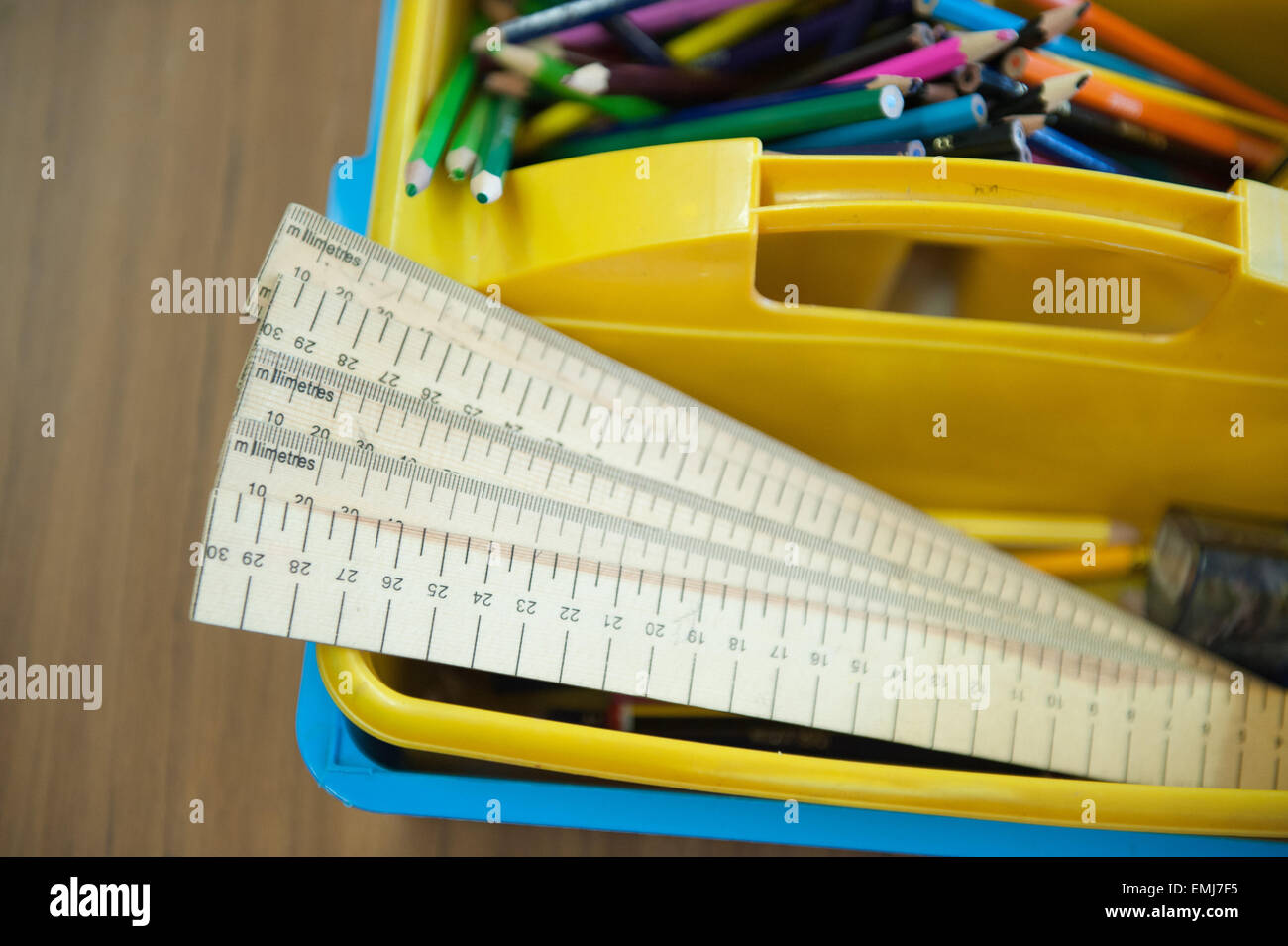 A box of rulers and coloured pencils in a UK classroom - Stock Image