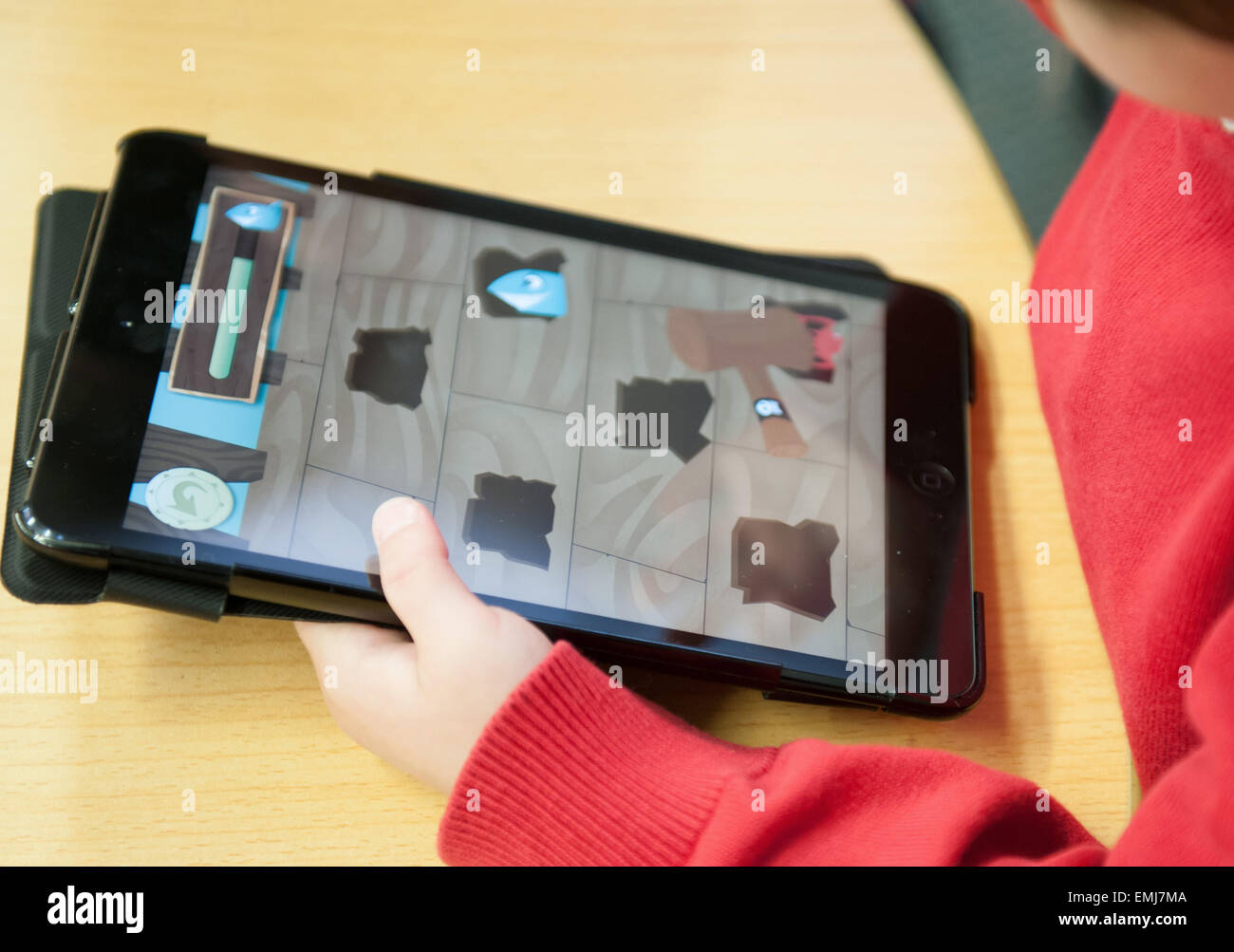 A UK primary school pupil using an ipad in a lesson in class - Stock Image