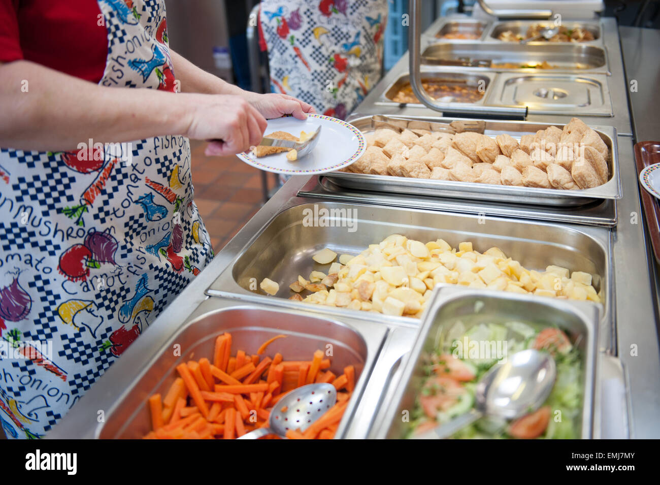 Dinner ladies at a UK primary school serve up hot dinners at lunchtime Stock Photo