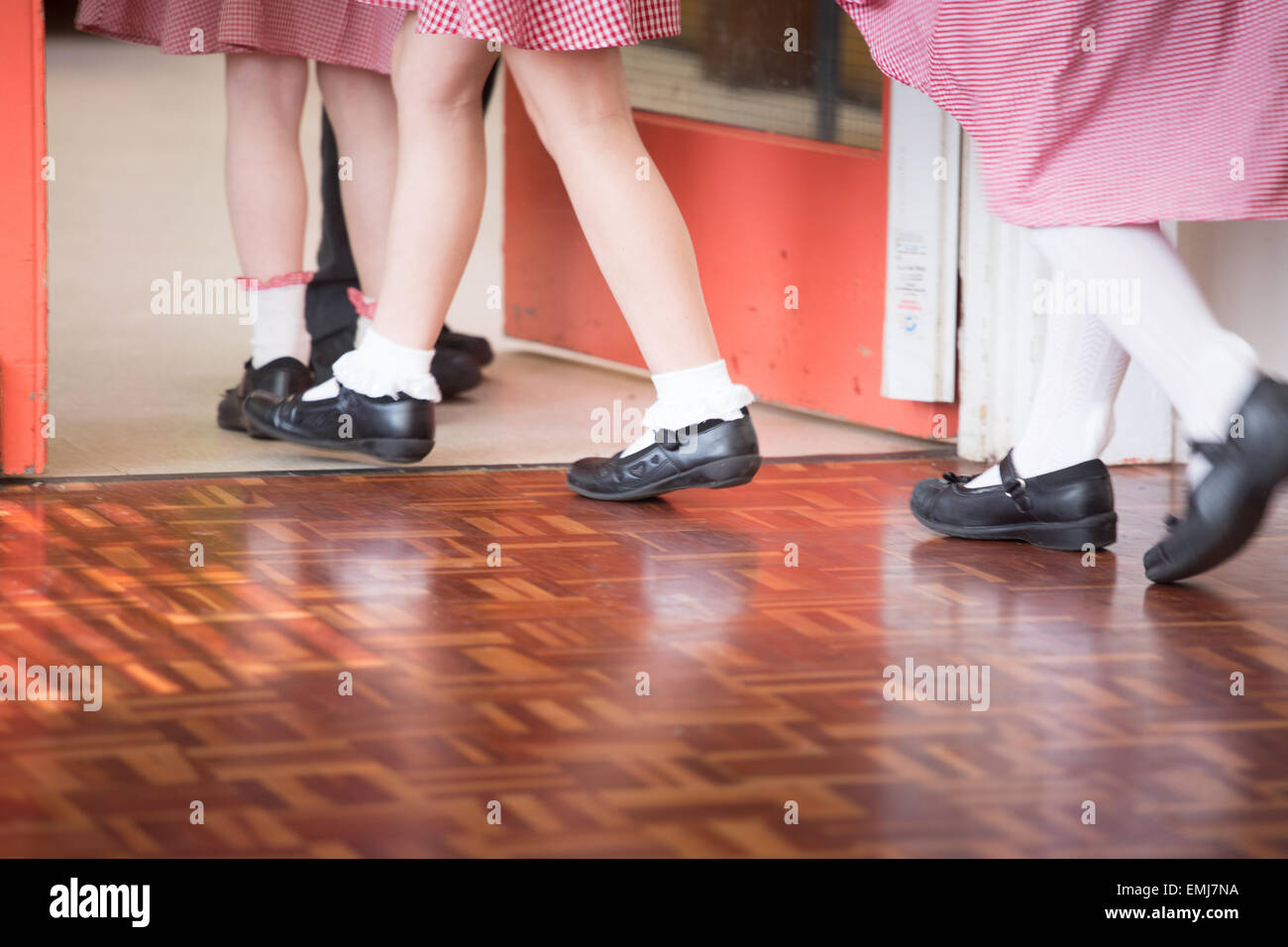 A group of UK primary schoolchildren leave the school hall after assembly - only legs and feet showing. - Stock Image