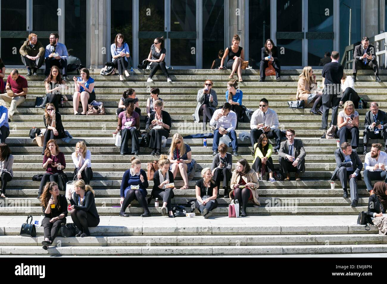 Sunny weather in Manchester city centre today (Tuesday 21st April 2015). Lunch on the steps of Manchester Crown - Stock Image