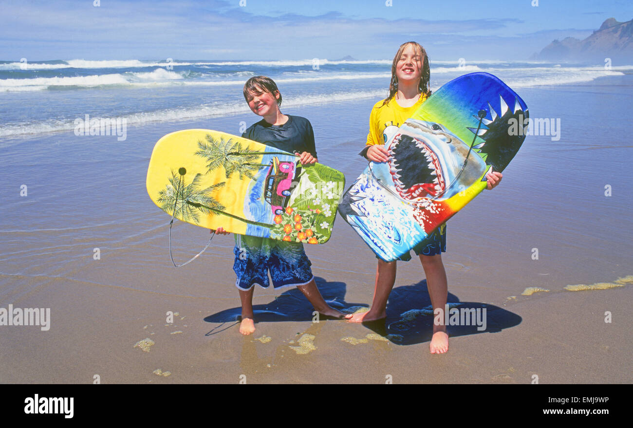 Two pre-teen girls with boogie boards on a beach on the Oregon Pacific  coast near the town of Lincoln city, Oregon