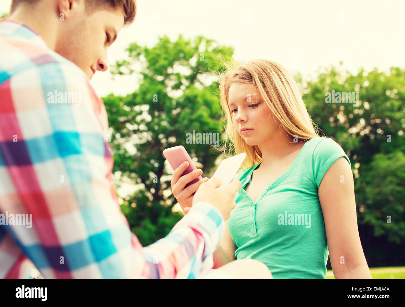 couple with smartphones in park - Stock Image