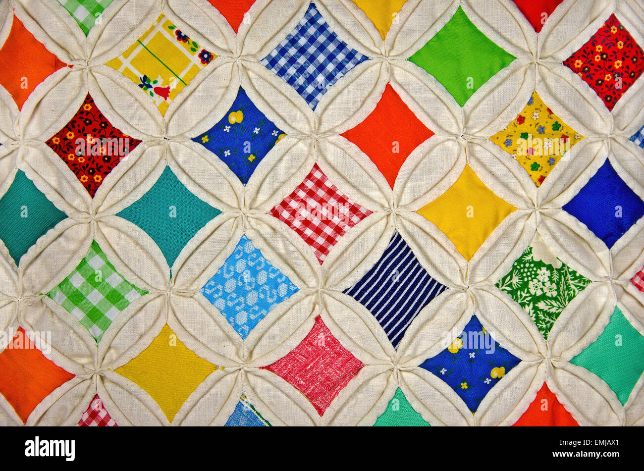 Colorful cathedral window quilt with muslin. - Stock Image