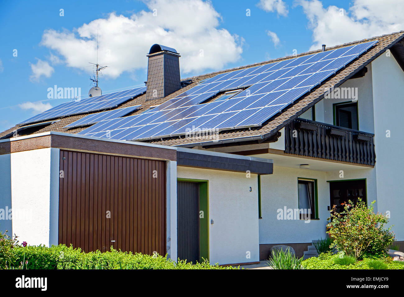 A house with solar panels on the roof - Stock Image