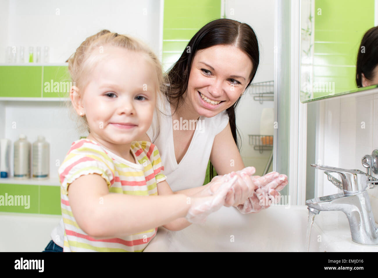 young woman and her daughter washing hands with soap in bathroom - Stock Image