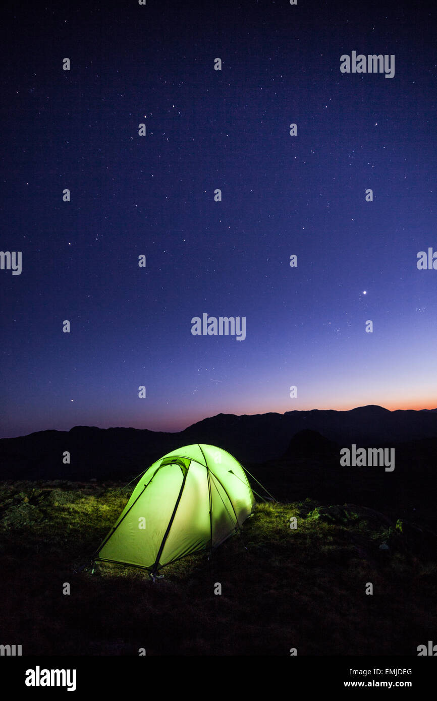 Torch lit wild camp tent after sunset as the stars come out in the dark skies, great langdale, english lake district - Stock Image
