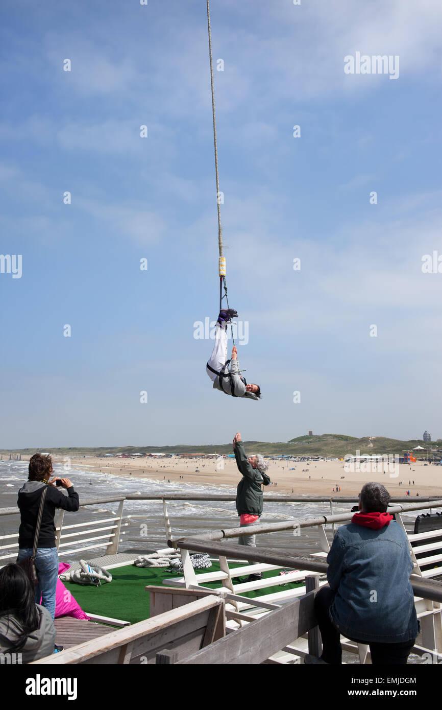 Woman hanging from a bungee jump cord at Scheveningen beach pier tower in Hague, (Den Haag), Holland, Netherlands. Stock Photo