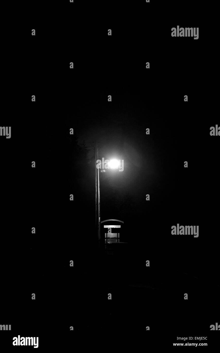 Streetlight shining above telephone box - Stock Image