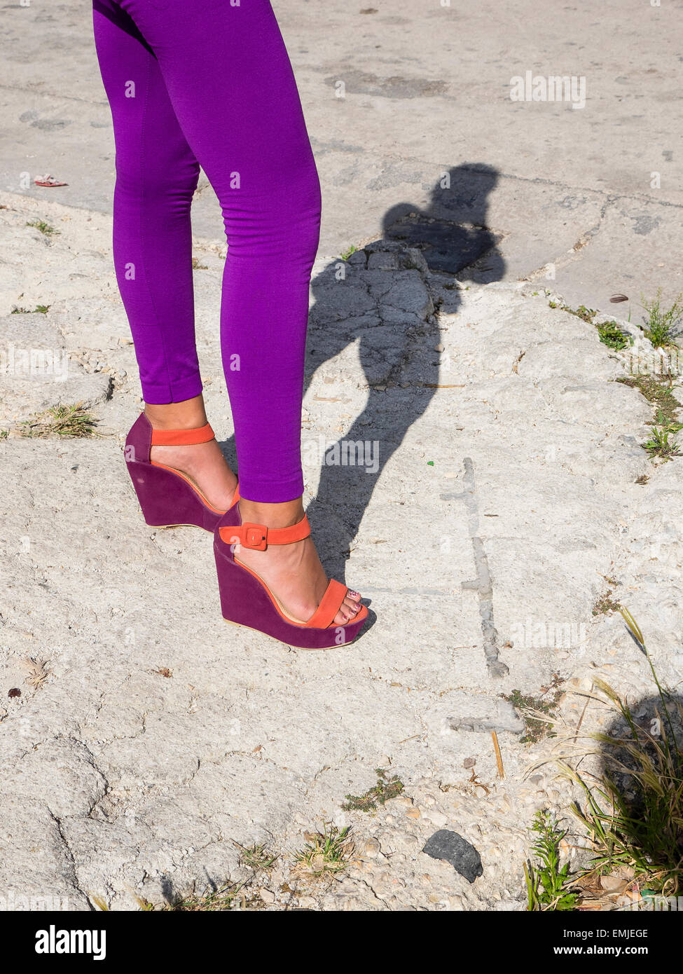 An image of a woman's purple tights, from waist down and purple and orange shoes. The woman casts a full figure - Stock Image