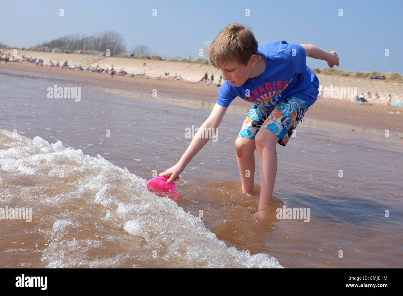 A boy collecting water in a bucket on a UK Beach - Stock Image