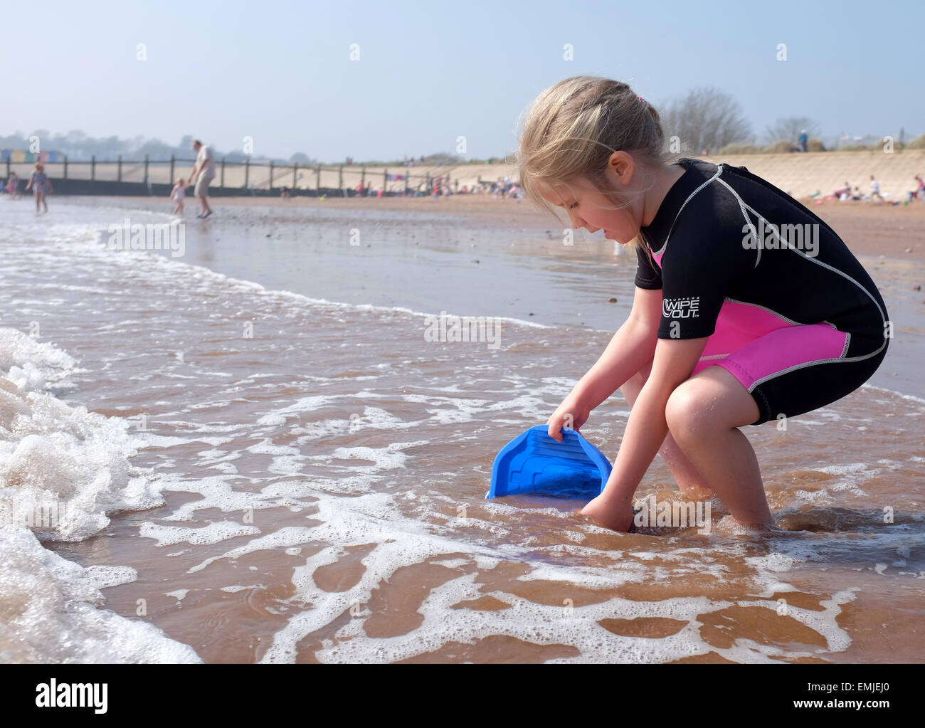 A young girl in a wetsuit collecting water with a bucket on the beach UK - Stock Image