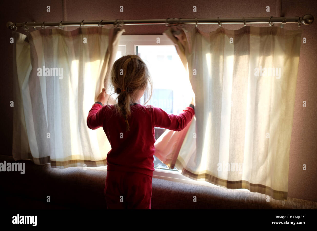 A sleepy young girl in pyjamas opens the curtains to look out of the window at the start of a new day - Stock Image