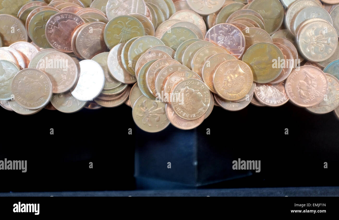 Two pence coins in a tipping point machine in a seaside arcade - Stock Image
