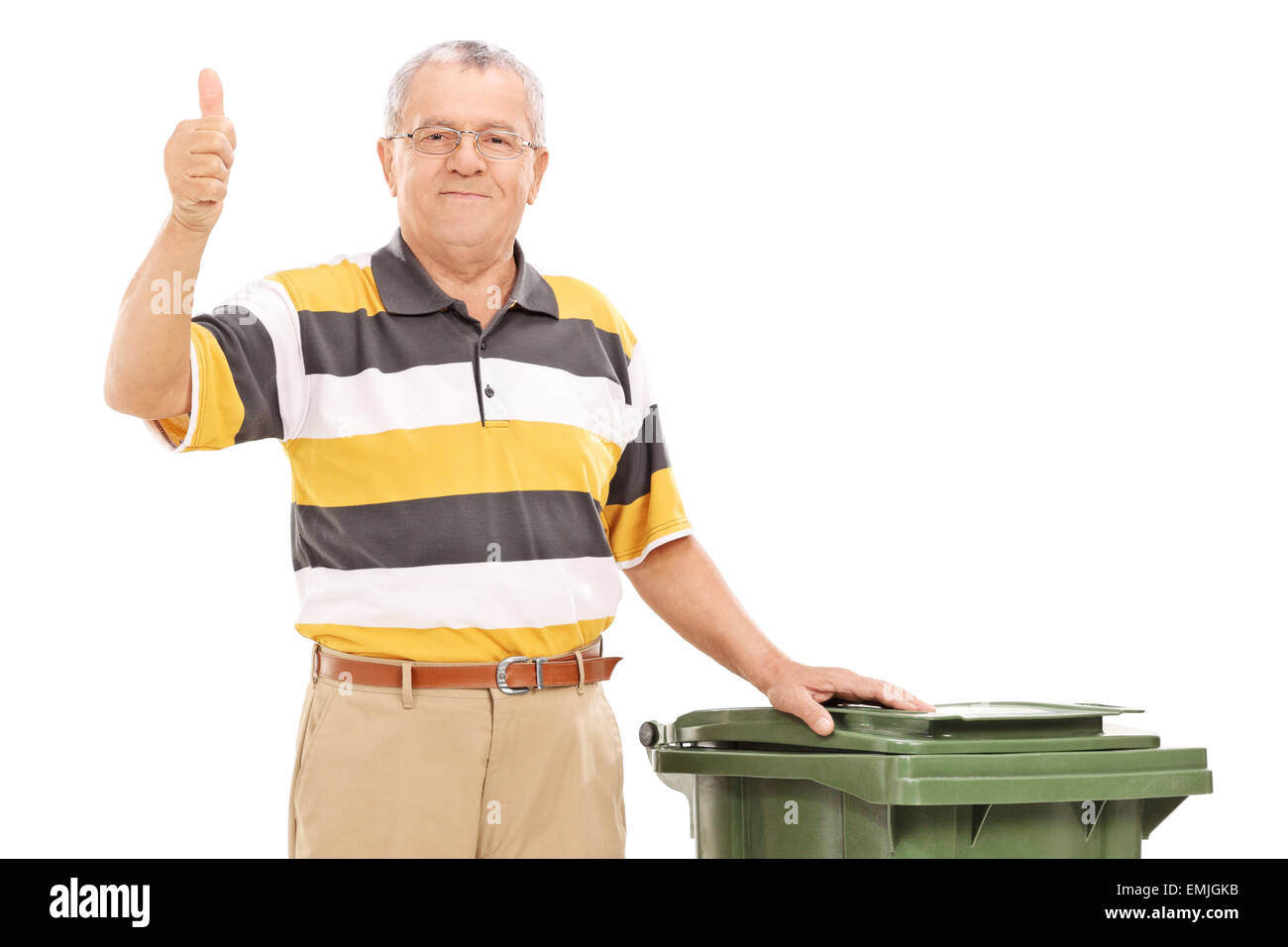 Satisfied senior standing by a trash can isolated on white background - Stock Image