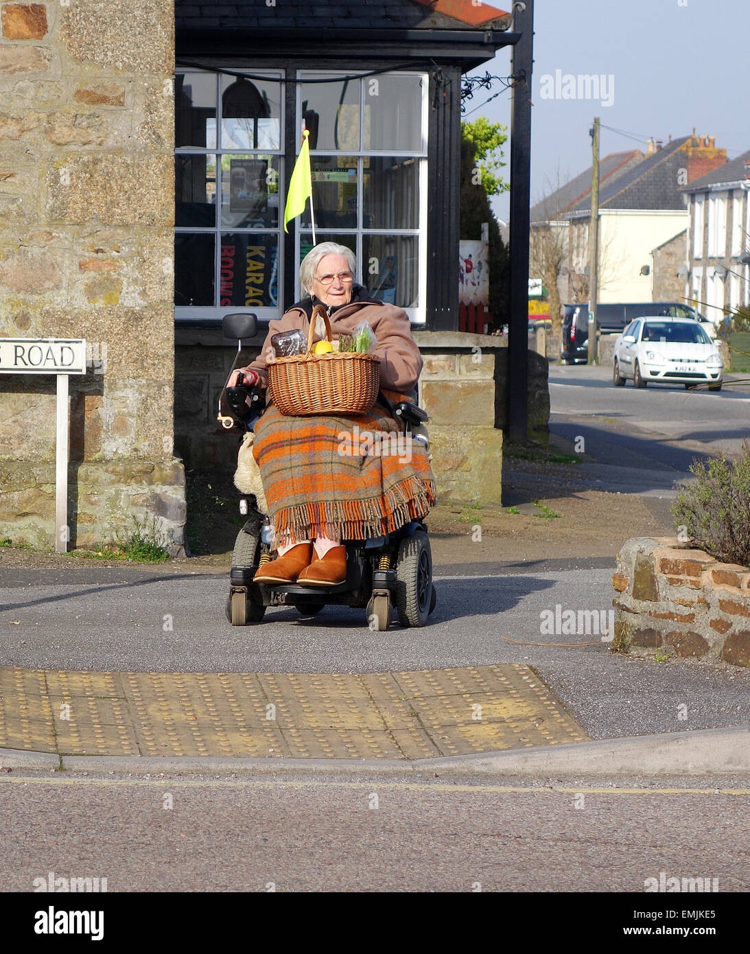 an elderly lady waiting  to cross the road on a mobility scooter - Stock Image