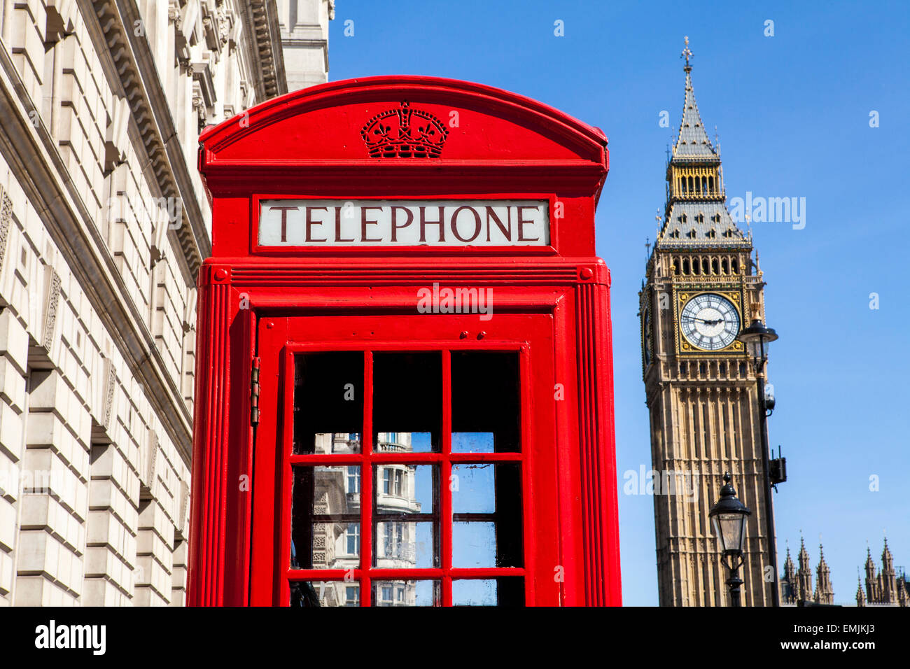 An iconic red Telephone Box with Big Ben in the background in London. - Stock Image