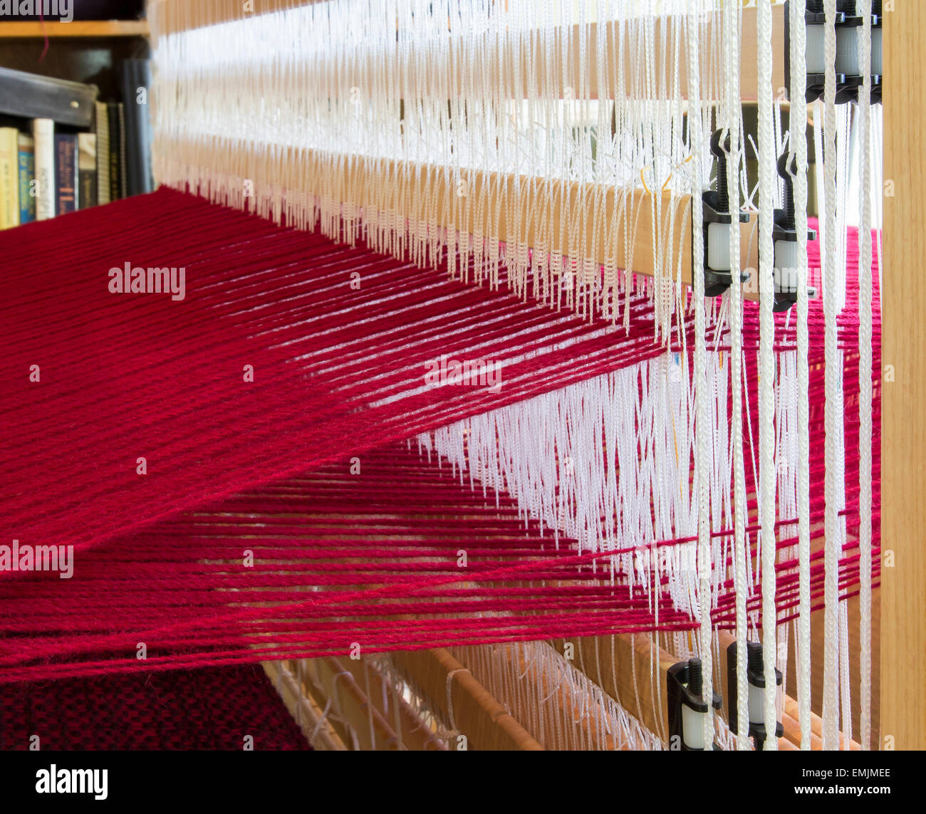 The white string heddles separate the red warp threads on this loom - Stock Image
