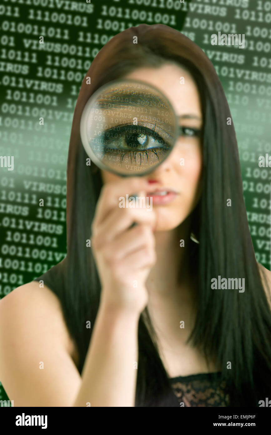 Woman looking through a loupe at a computer virus concept - Stock Image