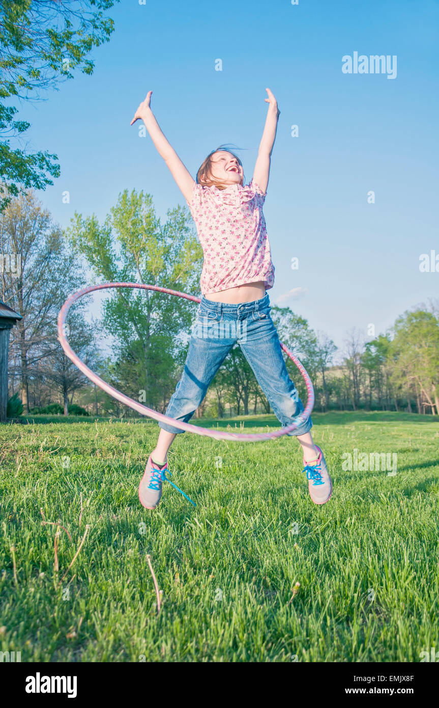 Girl jumping with hula hoop - Stock Image