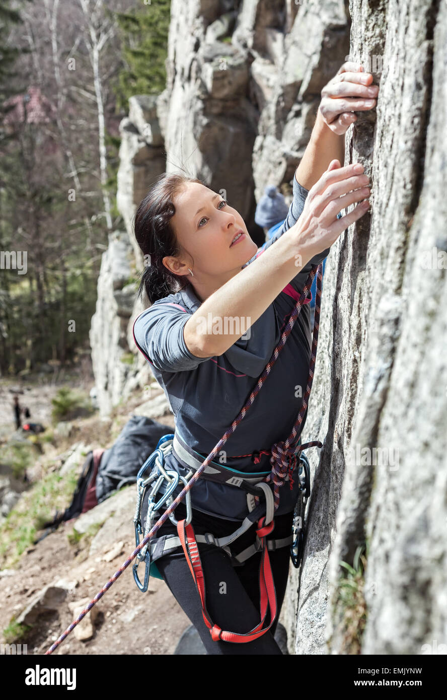 Portrait of a beautiful young woman climbing difficult wall. - Stock Image