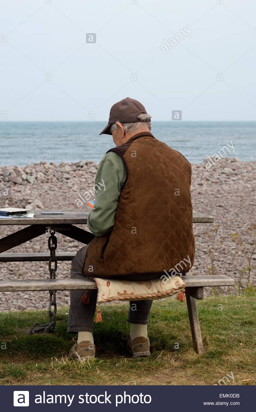 Older man sitting on a bench at the seaside on an overcast day - Stock Image