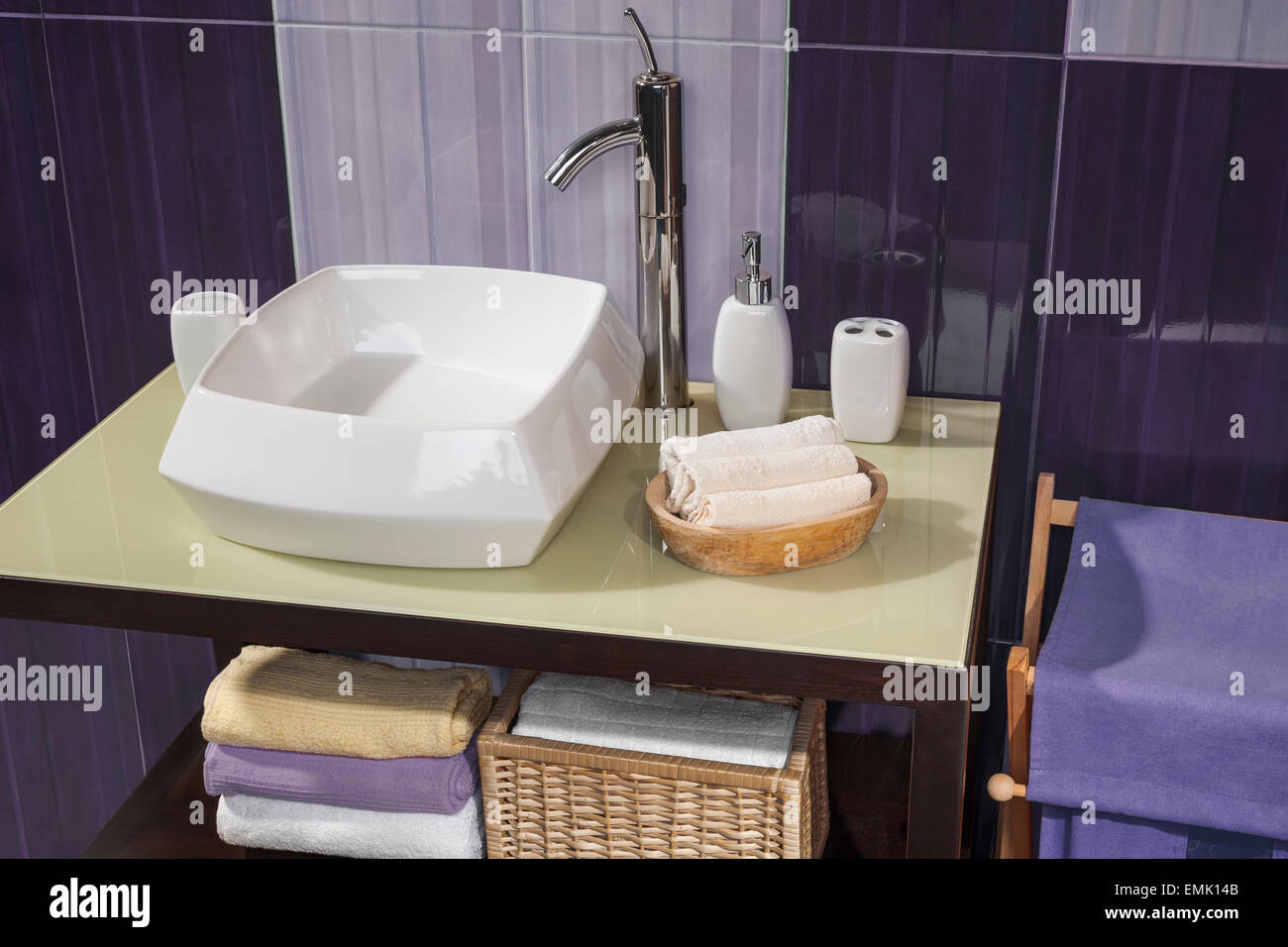 detail of a modern bathroom with sink and accessories, bathroom cabinet and purple bathroom tiles - Stock Image