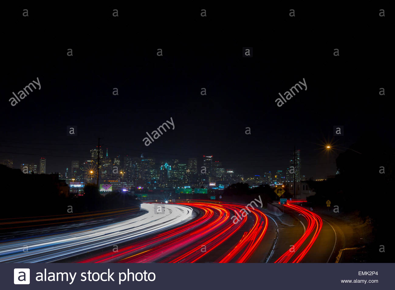 White and red light trail along urban road - Stock Image