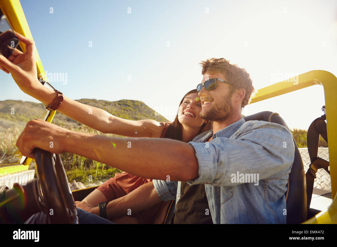 Couple on road trip, man driving a car and woman taking selfie on her mobile phone. - Stock Image