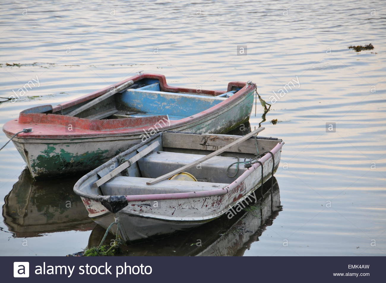 Two empty rowboats anchored side by side in calm water - Stock Image