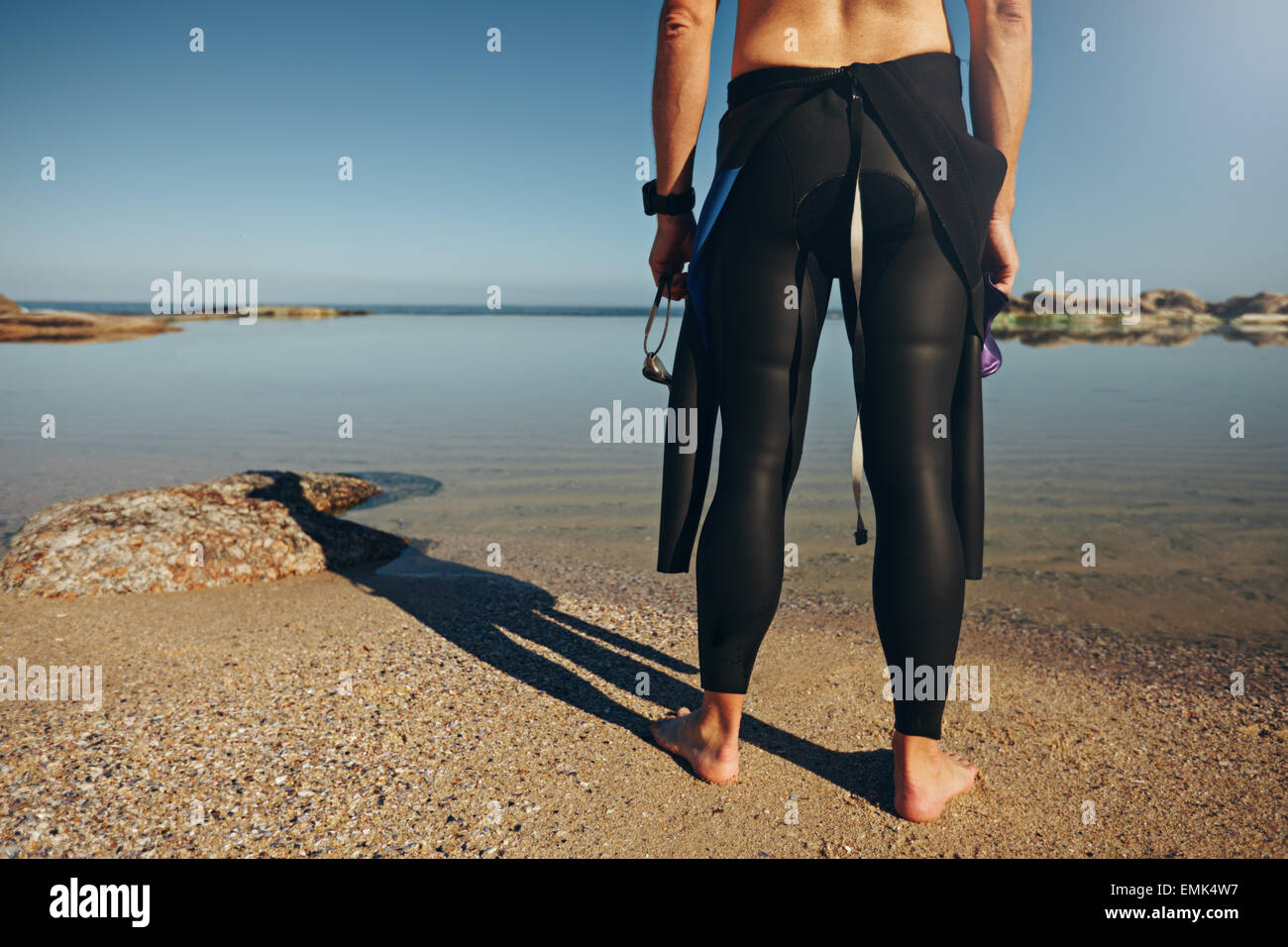 Rear view of man standing on lake wearing wetsuit. Cropped shot of a triathlete getting ready for a race. Stock Photo