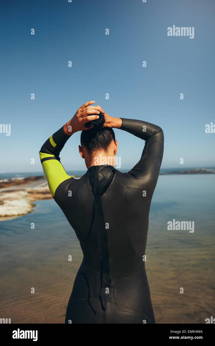 Rear view of young triathlete on the lake preparing for a race wearing a wetsuit. Female triathlon athlete tying - Stock Image