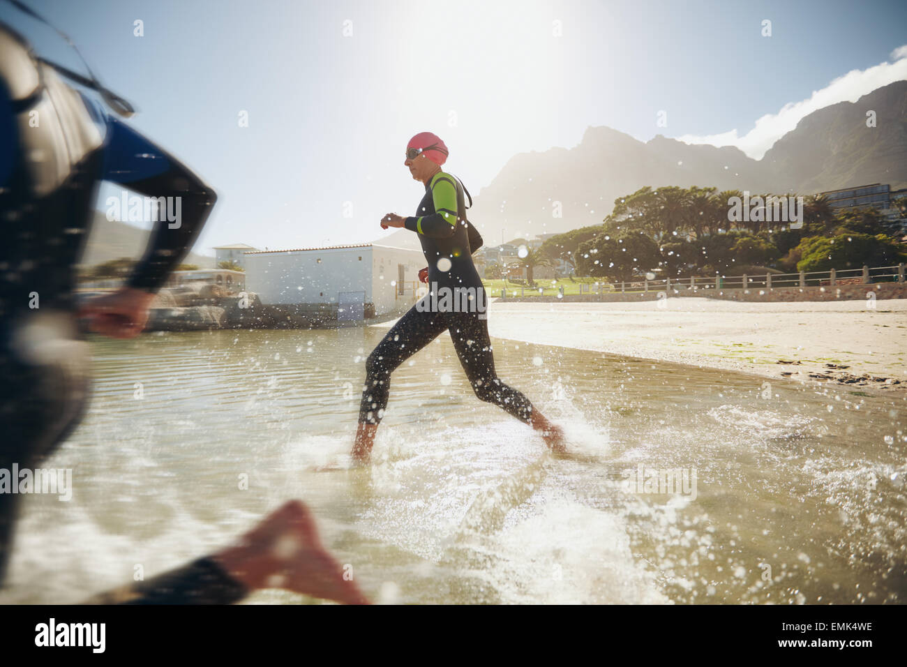 Participants running into the water for start of a triathlon. Two triathletes rushing into water. - Stock Image