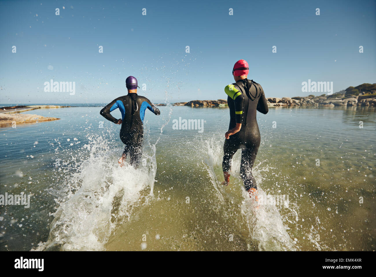 Two athletic swimmers entering the water with their wetsuits on.  Competitors in wet suits running into the water - Stock Image